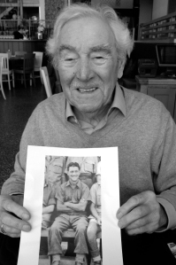 Bill Rae, 94, holding a 1941 photo of himself as a Prisoner of War in Italy.