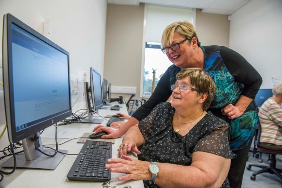Mary being helped to use a computer