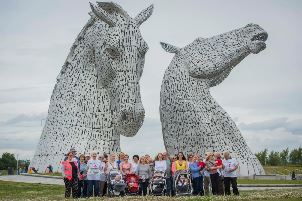 A large group up people standing in front of The Kelpies landmark