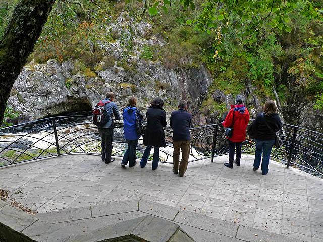 People standing on balcony overlooking Falls of Shin