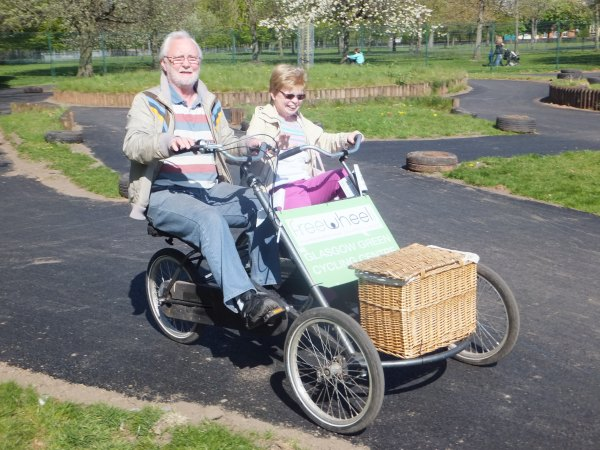 Older man and woman on a side by side tandem bike.