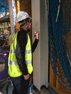 Big Lottery Fund Funding Officer writing name on skeletal infrastructure of a new community hub