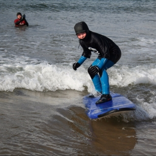 A young person surfing in the sea with a support worker behind him