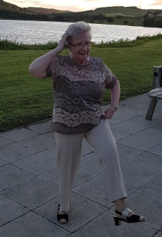 Betty, 83, flexing her legs and arms in front of a body of water