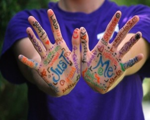 Colourful words written on the palms and fingers of someones hands