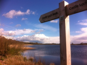 "Loch and the sky above, with a wooden sign reading ""Castle Loch Walk"" and ""Castle Lochmaben"""
