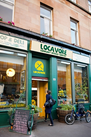 The green and yellow shopfront of the Locavore Community Interest Company, with a person walking through the front door