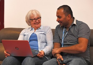 A man and an older women sitting together on a couch and working on a laptop