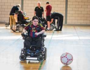 Young man in a powerchair moving towards a large football, in a gym