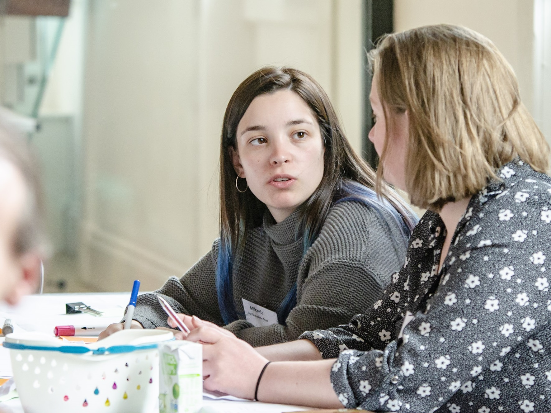 Young person talking to someone whilst writing ideas down