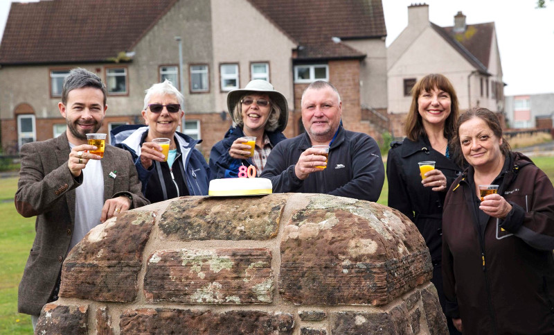 Group photo of smiling people with soft drinks and a cake at an event organised to celebrate the first social housing built in Lincluden 80 years ago