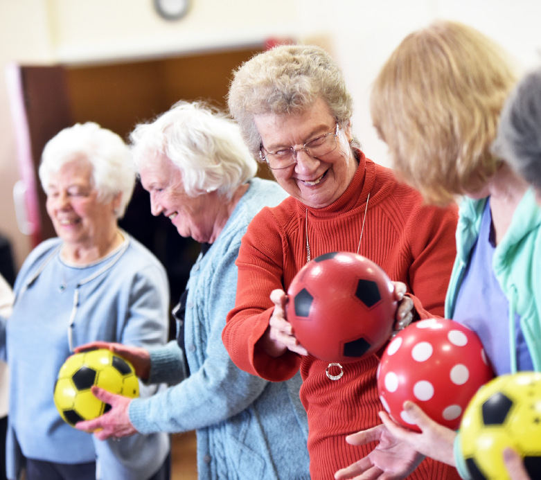 Older ladies passing balls to each other