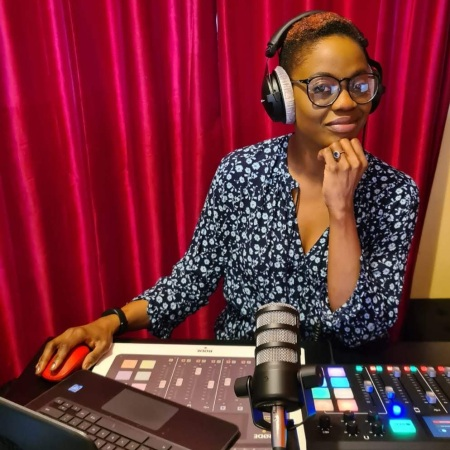 Jambo! radio presenter Bene Briggs-Mckinley wearing headphones and sat behind her laptop, microphone and mixing desk at her home studio.