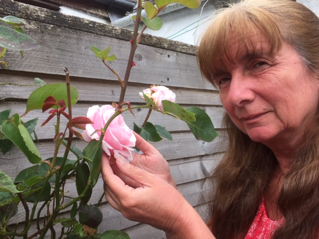 Issy McGrath, Co-Chair of Deafblind Scotland touching a rose in a garden