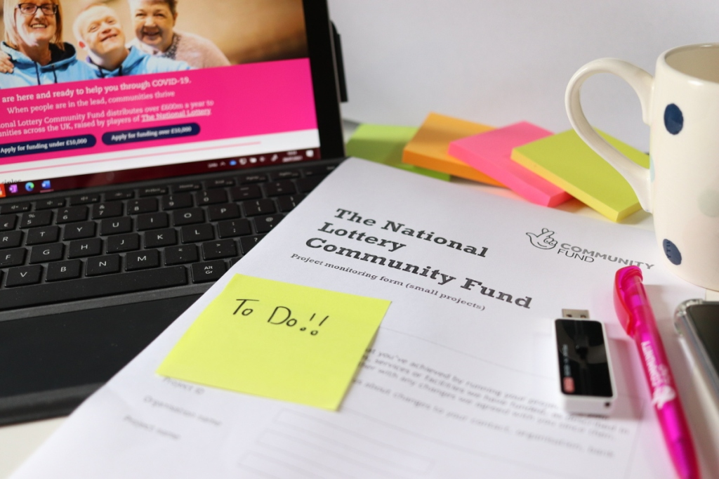 A grant reporting form lies on a cluttered desktop with a post-it note saying 'To Do!!' stuck to it.