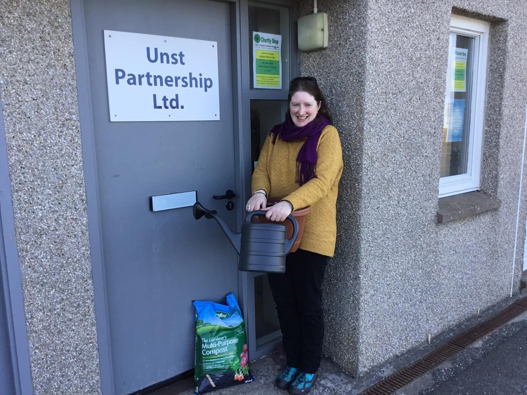 A woman standing in front of the Unst Partnership shop entrance holding a watering can.